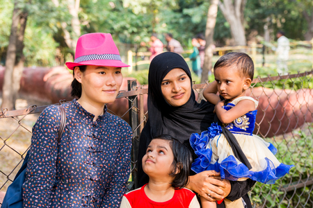 Hyderabad City, Andhra Pradesh, India- November 18, 2016: A smiling Chinese tourist taking photos together with an Indian Muslim family