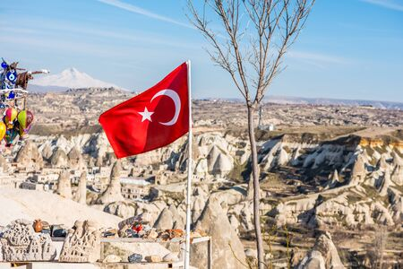 Turkish national flag with background of Goreme town, in Goreme national park. Cappadocia, Turkey
