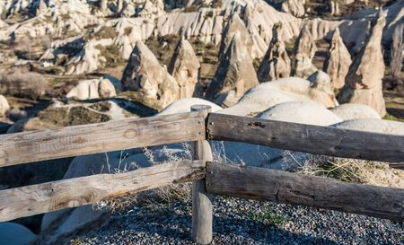 Wooden guardrail at the with background of vocanic rocks