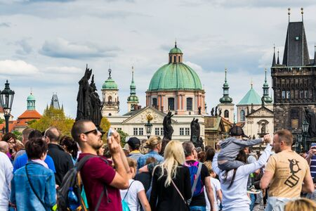 Lots of tourists walking at the bridge on the East side of the Charles Bridge, near the Old Town Bridge Tower and background of  Church of St Francis Seraph during the labor's day Stock Photo - 130970411