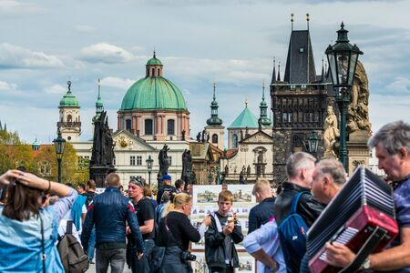 Lots of tourists walking at the bridge on the East side of the Charles Bridge, near the Old Town Bridge Tower and background of  Church of St Francis Seraph during the labors day Editorial