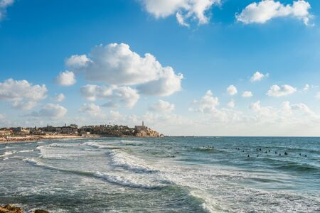 Old Jaffa city, old port and coastal line of Tel Aviv under sunset and lots of tourists are swimming and surfing at the Mediterranean sea. Reklamní fotografie