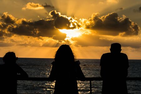 Beautiful sunset and golden twilight, and clouds, Silhouettes of people standing on the coast of Mediterranean sea in Israel and watching the sunset