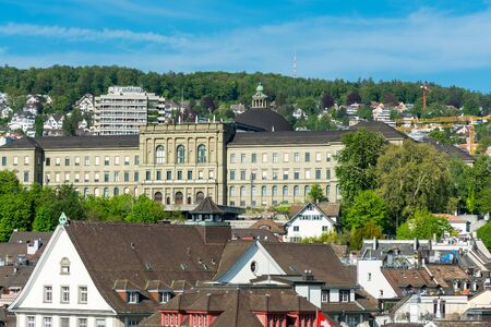 View of the historic center of Zurich at the bank of Limmat River, with beautiful house rooftops and main building of ETH , view form Lindenhof hill. 免版税图像