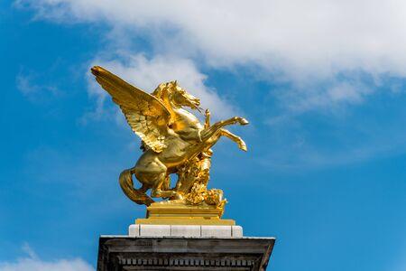 Golden pegasus statue at the Pont Alexander III bridge, Paris, a deck arch bridge that spans the Seine in Paris, France