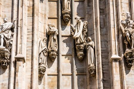Architectural details with statues on the wall of beautiful building of the Milan Cathedral (Duomo di Milano), the cathedral church of Milan, Lombardy, Italy. Dedicated to the Nativity of St Mary.