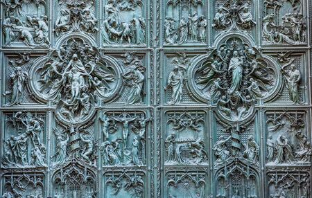 Beautiful bas-reliefs on the bronze door of  building of the Milan Cathedral (Duomo di Milano), the cathedral church of Milan, Lombardy, Italy. Dedicated to the Nativity of St Mary.