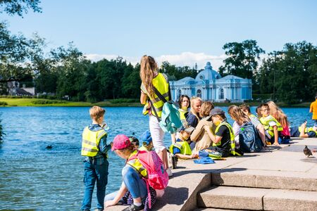 School kids at the lakeshore of the Great Pond in the Catherine Palace , a Rococo palace, the summer residence of the Russian tsars in St. Petersburg, Russia