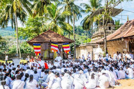 Buddhist pilgrims in the pavilions hall of shrine of Sri Dalada Maligawa or the Temple of the Sacred Tooth Relic, in Kandy, Sri Lanka, celebrating the the Vesak day, or Buddha Jayanti, Buddha Day.