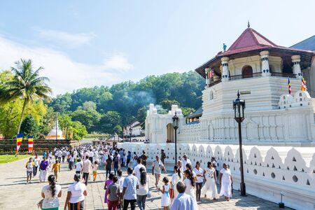 Buddhist pilgrims walking into the shrine of Sri Dalada Maligawa or the Temple of the Sacred Tooth Relic, in Kandy, Sri Lanka, celebrating the the Vesak day, or Buddha Jayanti, Buddha Day.
