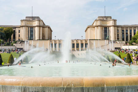 Tourists swimming at the fountain in front of the Palais de Chaillot,  a building at the top of the Chaillot hill in the Trocadero area in the 16th arrondissement of Paris, France.