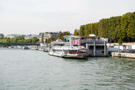 Cruise ship parking at the dock in the Seine river on a sunny day in Paris, France.