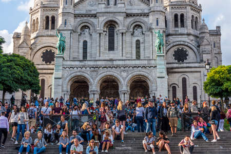 Tourists stroll in Montmartre near Basilica Sacre Coeur (designed by Paul Abadie, 1914) - a Roman Catholic Church and minor basilica, dedicated to Sacred Heart of Jesus.