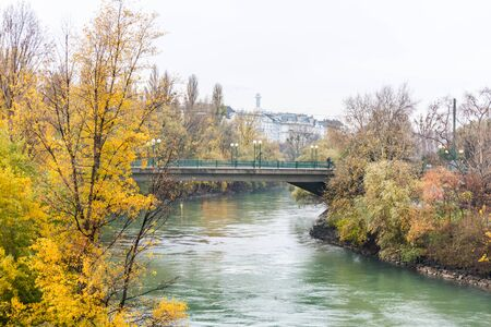 Landscape with buildings and yellow trees and bridge at the riverbank of Donaukanal (Danube cannal)  in a rainy day,  , in Vienna, Austria.  Imagens