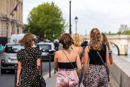 A group of female tourists walking at the street at the Ile de la Cite, one of two remaining natural river islands in Paris, France. 스톡 콘텐츠