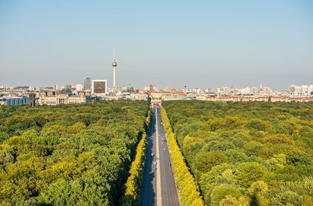Panoramic city view of Berlin, viewfrom the top of the Berlin Victory Column in Tiergarten, Berlin, with modern skylines and green forest.