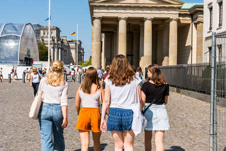 A group of female tourists walking to the Brandenburg Gate is an 18th-century neoclassical monument in Berlin