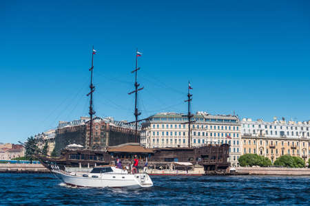 Old wooden ship on the Neva river and building on the riverbank in St. Petersburg, Russia. Editoriali