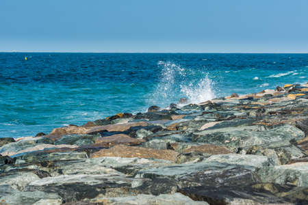 Waves of Persian Gulf splashing the stones of breakwater at the crescent road in the Palm Jumeirah island in Dubai of the United Arab Emirates. 版權商用圖片