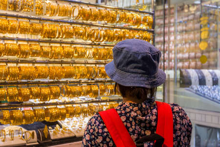 A Chinese woman wearing a hat and watching the golden jewelry at the gold street, also called Gold souk, in the city of Dubai, UAE