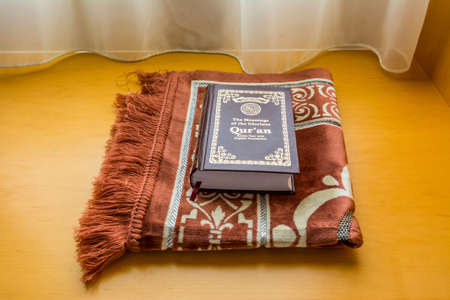 A holly Quran book on a traditional Arabic carpet at the window under sunlight at the room of hotel