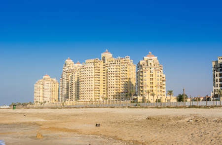 Tall residential buildings next to the beach against blue sky at Ras Al Khaimah, UAE