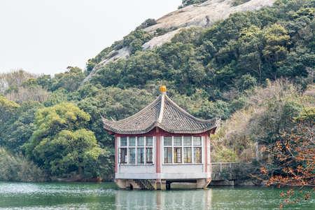 Chinese traditional pavilion next to lake in the Putuoshan mountains, Zhoushan Islands, a renowned site in Chinese bodhimanda of the bodhisattva Avalokitesvara (Guanyin)