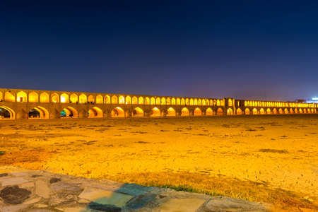 Arches of night view with light effect of Allahverdi Khan Bridge, also named Si-o-seh pol bridge across the Zayanderud river in Isfahan, Iran, a famous historic building in Persian History