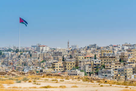 Cityscape of Amman with numerous buildings and Jordanian national flag, the capital and most populous city of Jordan, view from Amman Citadel, known in Arabic as Jabal al-Qal'a.