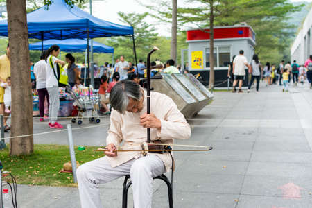 Mid-aged Chinese street musician playing Chinese traditional musical instrument-Erhu (Chinese Violin) in the Central Park of Shenzhen, China