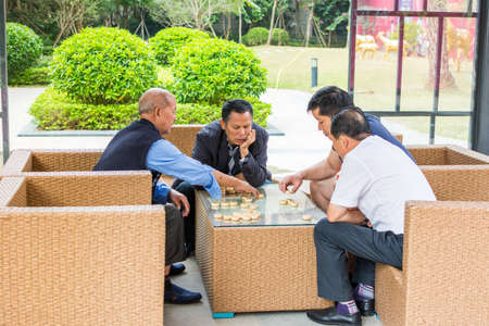 Four Chinese men playing Chinese chess in a park in Shenzhen, China