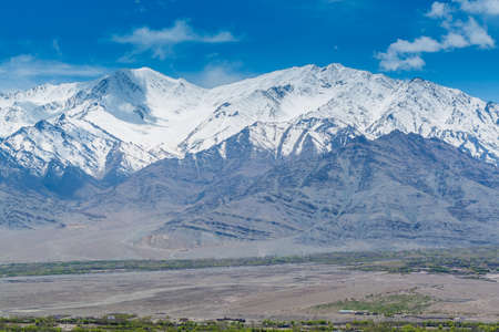 Beautiful landscape with fields of delta of Indus River, Tibetian buildings, Himalayas snow mountains, and blue sky, in Ladakh, Kashmir, view from Thiksey Monastery or Thiksey Gompa.