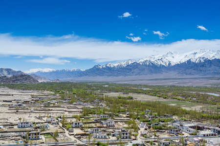 Beautiful landscape with fields, Tibetian buildings, snow mountains, and blue sky, in Ladakh, Kashmir, view from Thiksey Monastery or Thiksey Gompa
