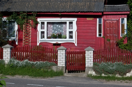 The front of red wooden house with white window, fence and gate Stock Photo - 20287739