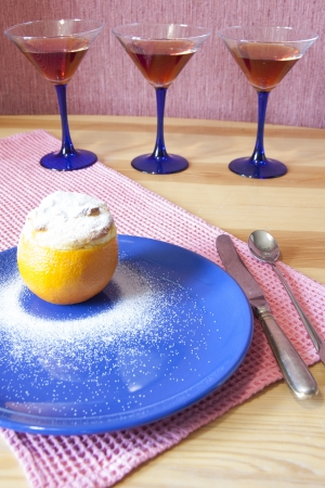 Orange dessert served with a knife, a spoonon and martini glass. photo