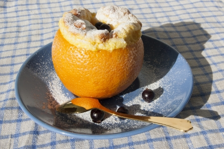 Orange dessert served with a golden spoon on the blue plate. photo