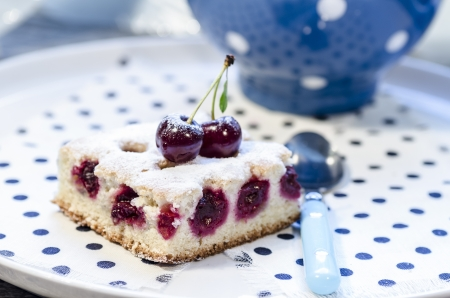 A slice of cherry pie on a linen napkin with polka dots. A cake decorated with fresh cherries. Next to a glass of juice. From the series Homemade Cherry Pie photo