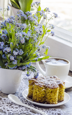 Polenta cake with cup of Coffee. Near forget me nots on rustic wooden table. photo