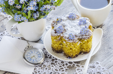 Polenta cake with cup of Coffee. Near forget me nots on rustic wooden table.
