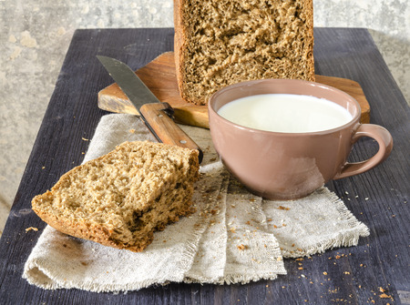 Homemade bread on cutting board with cup of milk From series Homemade bread photo