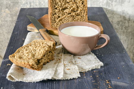 Homemade bread on cutting board with cup of milk, blurred background From series Homemade bread photo