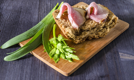 ooking: Two slices of smoked meat on bread with fresh herbs, selective focus From series Сooking meat Stock Photo