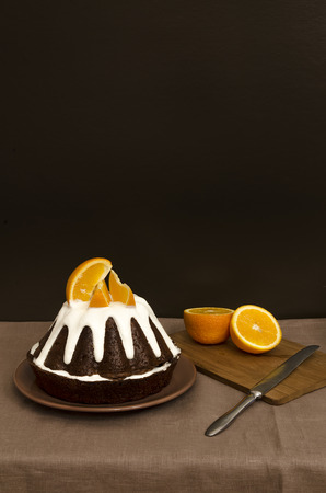 Chocolate orange cake covered with icing. Low key. From the series Cooking orange dessert photo
