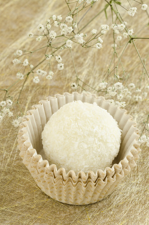 sweats: White, round, coconut chocolate sweats on golden background with flower From series elegant desserts