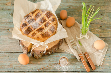 Neapolitan Easter cake with ricotta and wheat on old wooden table. Next egg, knife and fork. Rustic style. Stock Photo
