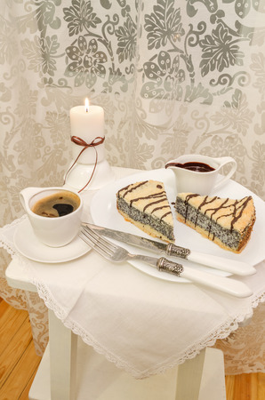 German poppy seed cake on white plate with chocolate and coffee photo