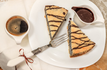 German poppy seed cake on white plate with chocolate and coffee
