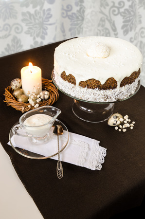 easter candle is burning: Easter cake with cream  icing and burning candle. Festive table decorated nest, quail eggs and candle.