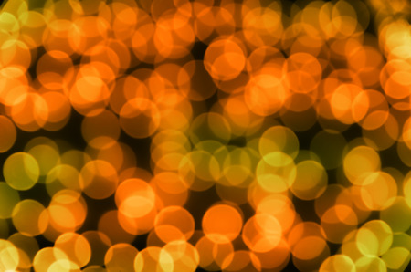 irish easter: Festive colored glowing abstract circular bokeh orange green background. Best for greeting card, web  banner. Stock Photo