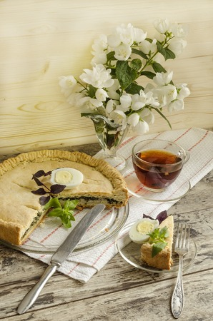 Pie with spinach and egg. Near a cup of tea with lemon and a beautiful bouquet of jasmine. photo